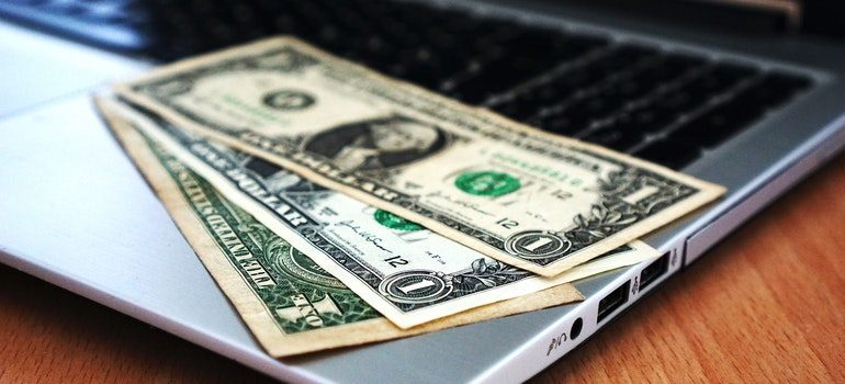 Dollar bills on a laptop.