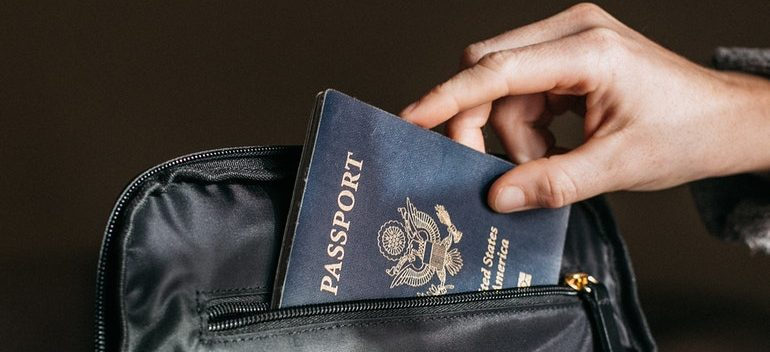 Person putting a passport in their bag.