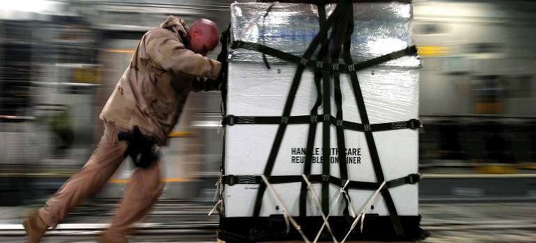 A man pushing a crate