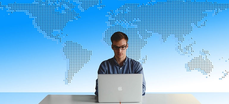 A man working on computer in front of world map