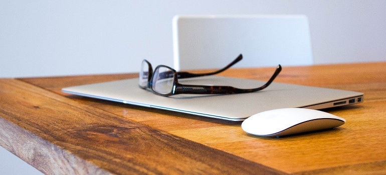 Glasses laptop and a mouse on a wooden desk