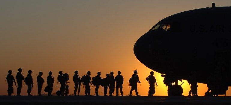 Military people boarding a plane.
