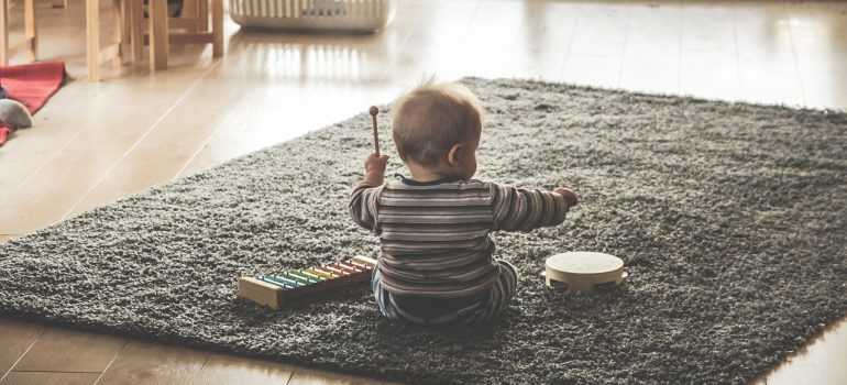 A toddler playing with a xylophone