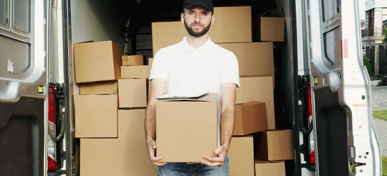 Man holding a box in front of the moving van