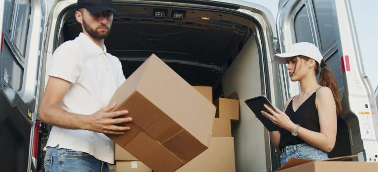 male and female standing next to the van with moving boxes