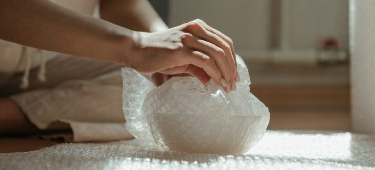 person using bubble wrap to protect the item while packing