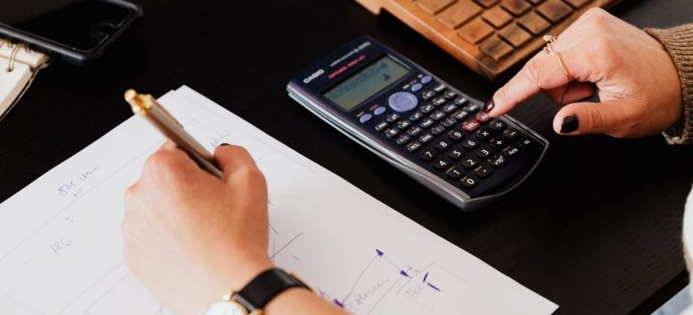 person writing and calculating