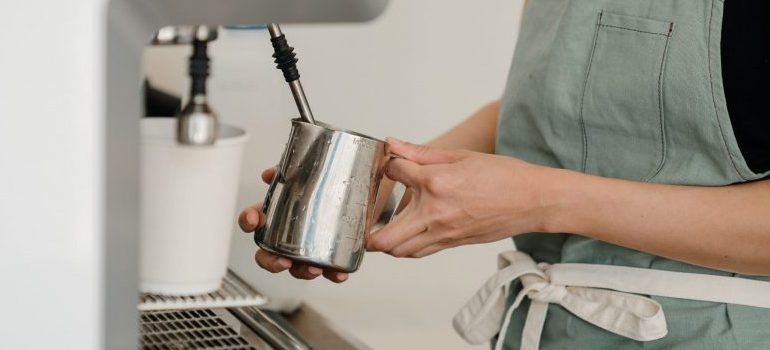 woman using coffee machine in the kitchen