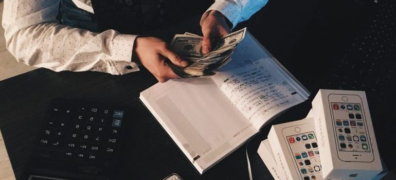 person holding money in hands, calculator on the table in front