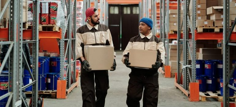 two males carrying moving boxes