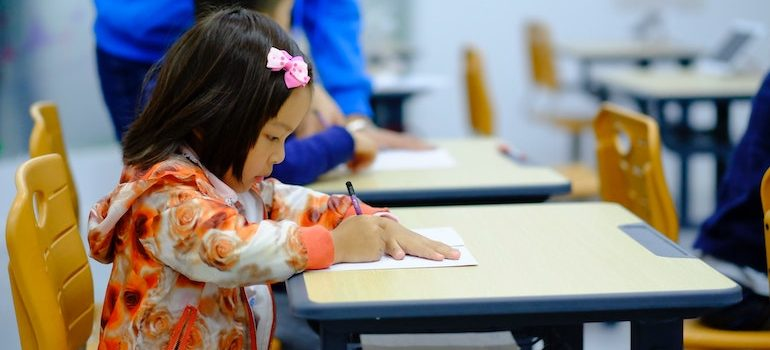 little girl sitting at the desk and drawing