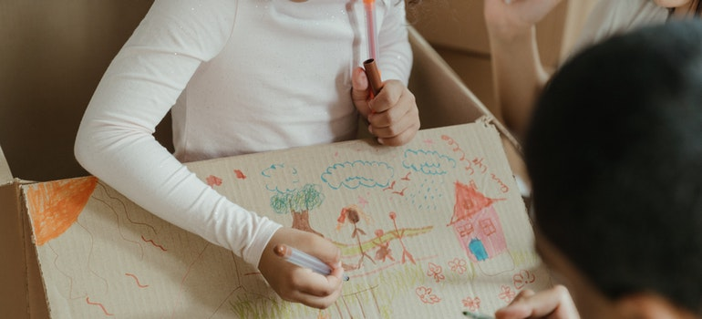 Kid drawing on a cardboard box
