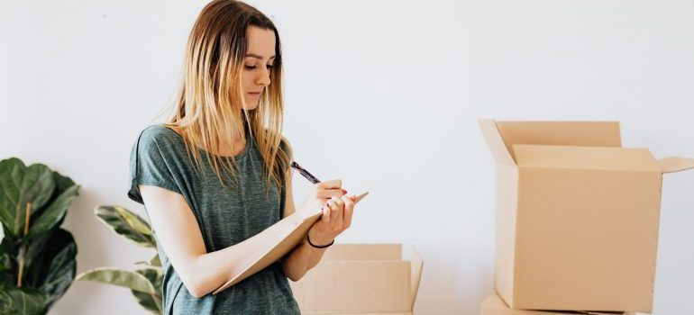 female creating a list, moving boxes in the back