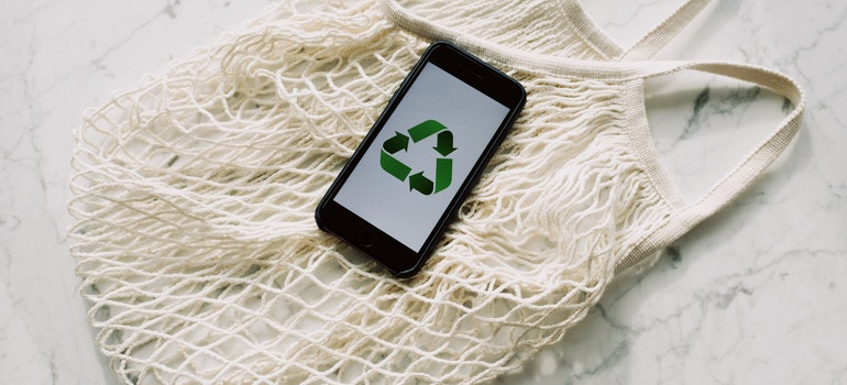Recycle sign on phone, on a net bag