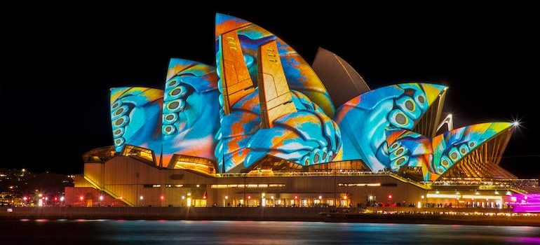 The Sydney State Opera at night covered in colorful projections