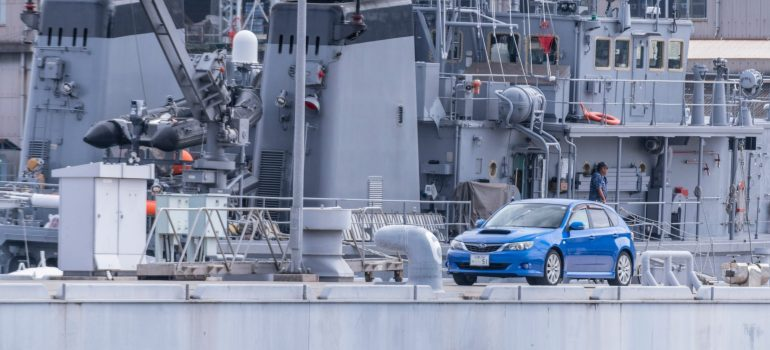 a blue car on a ship moving overseas