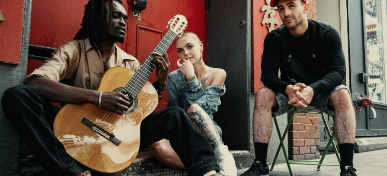 two men and a woman sitting on the side of the road playing the guitar