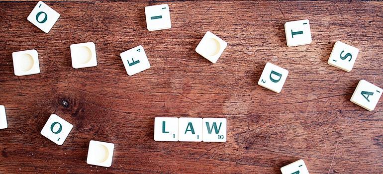 """Scrabble tiles, """"LAW"""" written on desk"""
