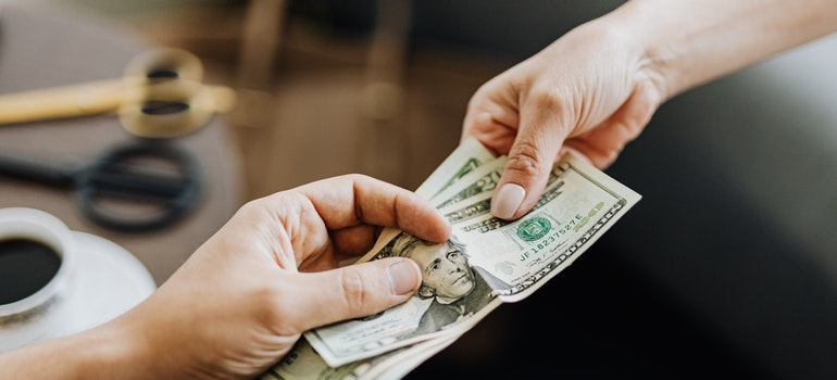 Two hands holding dollar notes
