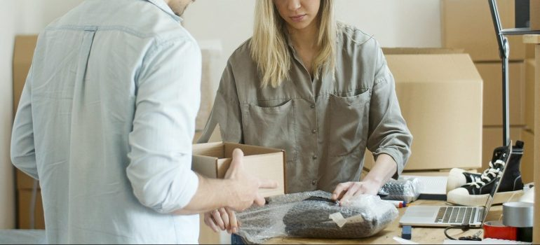 a man and a woman packing an item together