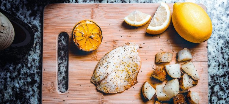 a chipping board with fish and lemon on it as the main part of Australian cuisine