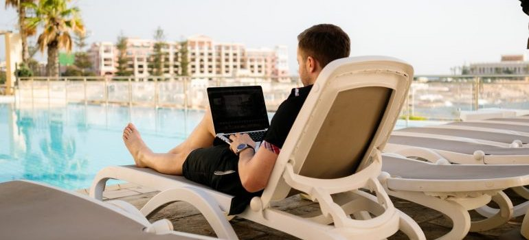 A person holding a laptop researching problems that expat could have