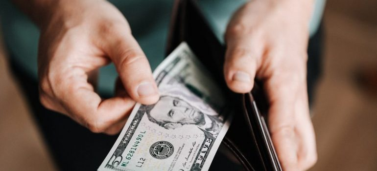 A man taking money out of his wallet because he has to pay more for shipping since the shipping industry has adapted to the new world.