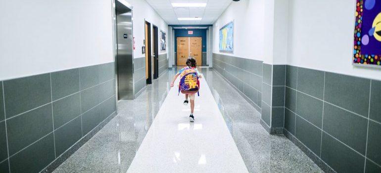 Kid running through a school coridor