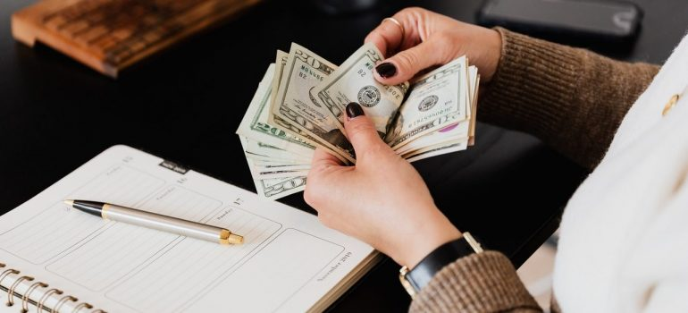 a woman counting money before moving from USA to Norway on a budget