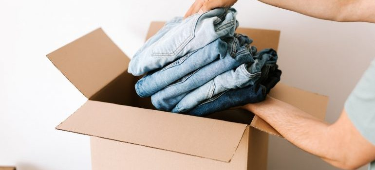 A person packing clothes in a moving box.