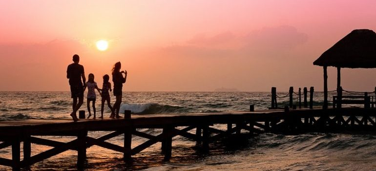 Family standing on a dock watching sunset